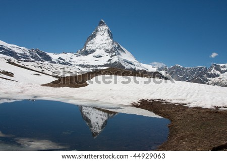 The Matterhorn reflected in a small lake. Early summer. - stock photo