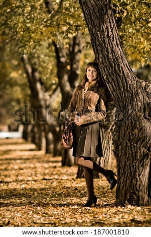 The  mature beautiful woman, walking outdoor in park, autumnal day - stock photo