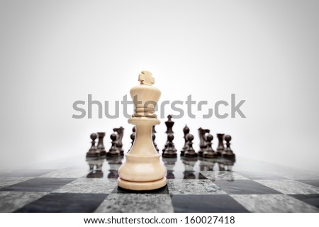 The meaningful photo of chess king staying before the set of another colour pieces. - stock photo
