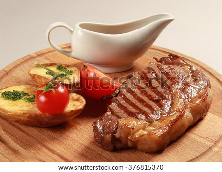 The meat on the grill with baked potato on a wooden platter