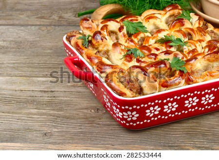 The meat pie made at home on a wooden surface. - stock photo