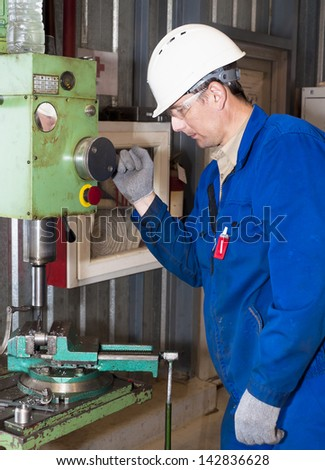 the mechanic dressed in overalls, works at the boring machine - stock photo
