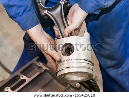 The mechanic holds the piston in hand before repair. - stock photo