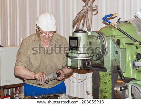 The mechanic operates the production equipment