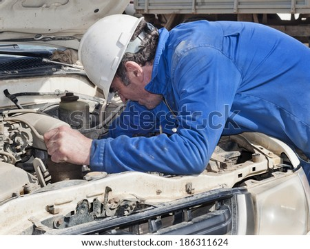 The mechanic repairs the car on the street - stock photo