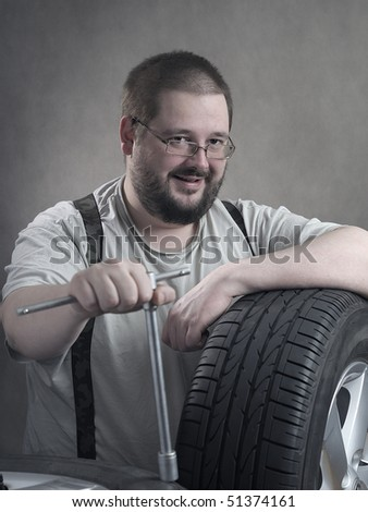 The mechanic with wrench and tyres