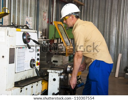 the mechanic works at the lathe at factory