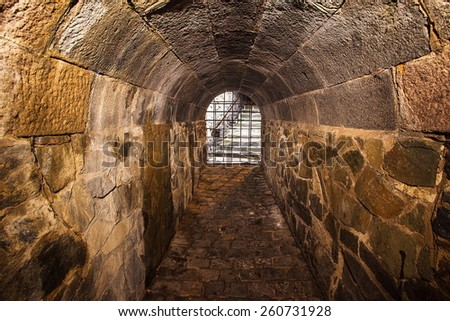 The medieval tunnel with a light in the end - stock photo
