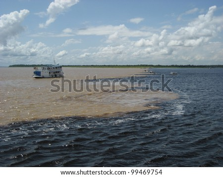 The Meeting of Waters (Portuguese: Encontro das Aguas) is the confluence between the Rio Negro, a river with dark (almost black coloured) water, and the sandy-coloured Amazon River or Rio Solimoes. - stock photo