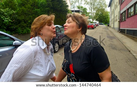 The meeting two middle aged women in summer - stock photo