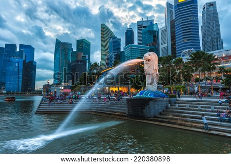The Merlion fountain lit up at against the Singapore skyline. - stock photo