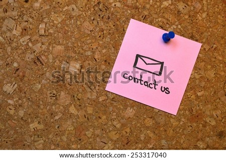 """The message """"contact us"""" on a pin board - stock photo"""