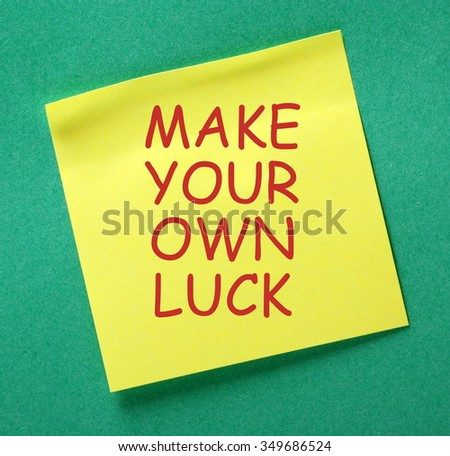 The message Make Your Own Luck in red text on a yellow sticky note posted on a green notice board as a reminder - stock photo