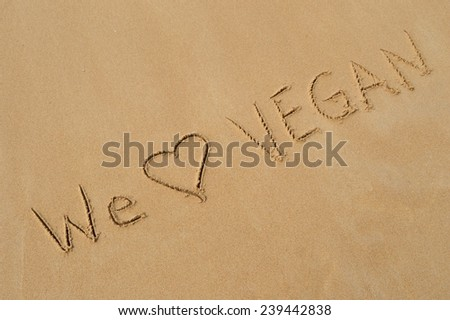 """The message """"we love vegan"""" written in the wet sand at the beach - stock photo"""