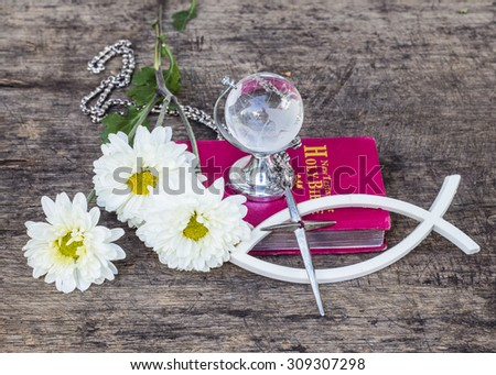The   metal cross  over the white christian fish and the world globe model on the red bible with white flowers on wooden background, world mission concept.  - stock photo