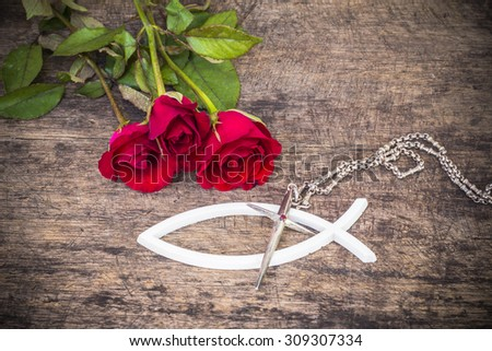 The metal cross  over the white christian fish and with red roses  on wooden background, world mission concept.  - stock photo