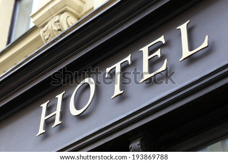 The metallic hotel sign on the wall - stock photo