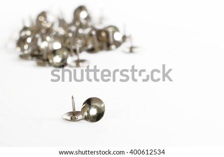 The metallic thumbtacks (drawing pins) on white background - stock photo