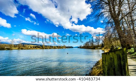 The mighty Fraser River as it flows past the historic village of Fort Langley in British Columbia, Canada on a nice winter day under blue sky and some clouds
