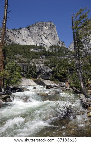 The Mighty Merced: The Merced River upstream of the world famous Vernal Falls in Yosemite National Park. Majestic Mount Broderick keeps watch over the river which is flanked by weathered pine trees.