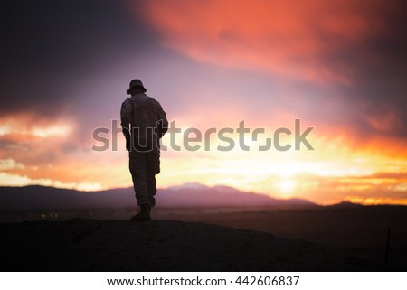The military stands on the rock on sunset background