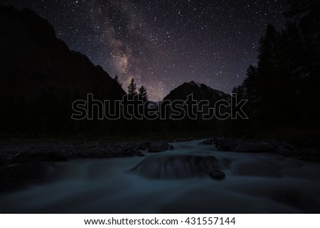 The Milky Way and the stars above the river and the forest. Night landscape - stock photo