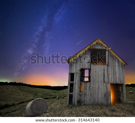 The Milky Way over a rustic barn. - stock photo