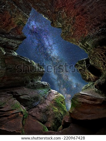 The Milky Way seen through an opening in a sandstone rock formation. - stock photo