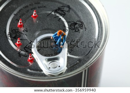 The miniature figure model of worker on aluminum can lid represent the food packaging business  concept related idea. - stock photo