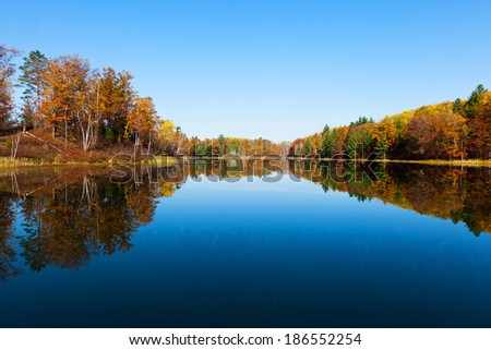 The mirror-like surface of this lake perfectly reflects the autumn colors displayed by the shoreline trees on this fall day in Michigan - stock photo