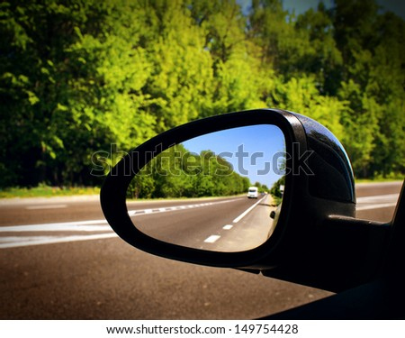 the mirror of the car with the road - stock photo