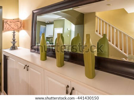 The mirror on the shelf with some decorative vases. Interior design.