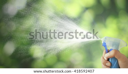 The mist spray bottle to spray water into the air, background bokeh leaves.