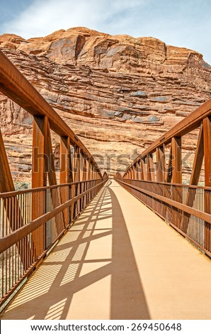 The Moab Canyon Pathway for pedestrians and bicyclists  begins at the pedestrian/bike bridge that crosses the Colorado River on Highway 128, just north of Moab. - stock photo