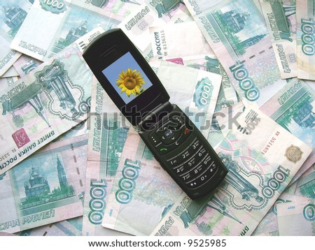 The mobile phone laying on banknotes of Russia