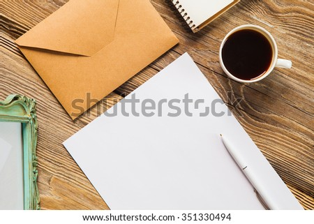 The mockup on wooden background with vintage old picture frame, pen, pencil, cup of coffee, white blank paper for writing, envelope and notebook