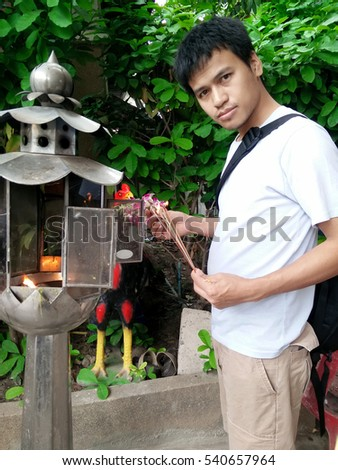 "The model name is ""SONGWUTH CHOMPOONGAM"" Asian man, He holding that the worship of Buddhism"