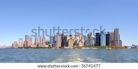 The Modern architecture of downtown manhattan as seen from over the battery park trees. - stock photo