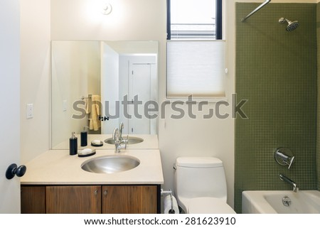 The modern bathrooms are in classic style architecture. Clean contemporary bathroom with green titled bath tub and teak Modern Bathroom vanity. - stock photo