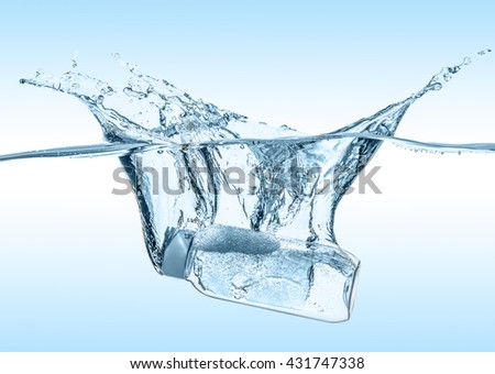 The moisturizing shampoo, cosmetic liquid, tonic, thermal water  falls into the  water with big  splash on the gradient blue background - stock photo
