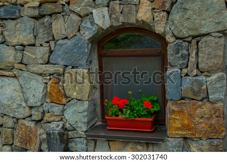 The monastery of stone, an old Church in the mountains. Alan Svyato-Uspensky monastery, which is located in Fiagdon.Hidixys.A window on stone wall background.Red flowers in a pot. - stock photo