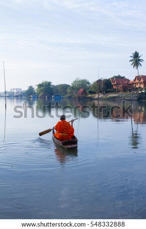 The monk oaring the boat on the river in the early morning to get the food from buddhist  people who donates for him