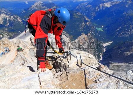 "The Monte Cristallo summit and woman climbing via ferrata ""Marino Bianchi"", Dolomite Alps, Italy - stock photo"