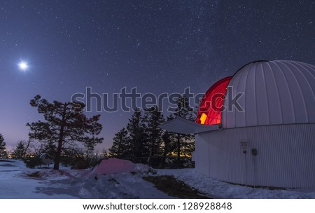 The moon lights up the observatory containing the Schulman telescope on Mount Lemmon during their Skycenter public outreach program. The city of Tucson, Arizona glows in the distance.