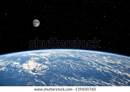 The Moon over planet Earth. Elements of this image furnished by NASA. - stock photo