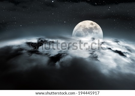 The moon rises over a region covered with clouds