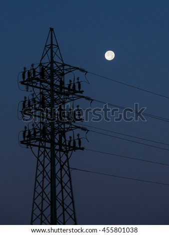 The moon seen at dawn next to a high voltage electrical tower