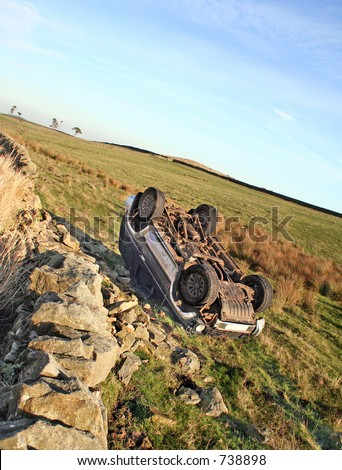 The morning after the night before. A four wheeled drive vehicle lies overturned after failing to take a bend and crashing through Stone wall, Police sign to side of veicle - stock photo