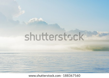 The morning mist rolling of the green coast of Cornwall UK from the calm sea. - stock photo