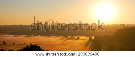 the morning mist, the factory and a large sun in the sky panorama - stock photo